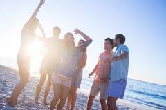 Amis heureux dansant sur le sable Photo stock