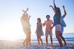 Amis heureux dansant sur le sable Photos libres de droits