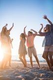 Amis heureux dansant sur le sable Photos stock