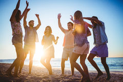 Amis heureux dansant sur le sable Photo libre de droits