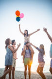 Amis heureux dansant sur le sable avec le ballon Photo stock
