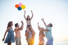 Amis heureux dansant sur le sable avec le ballon Photos stock