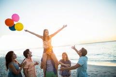 Amis heureux dansant sur le sable avec le ballon Images libres de droits