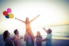 Amis heureux dansant sur le sable avec le ballon Photographie stock