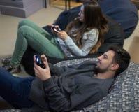 Amis heureux de couples jouant des jeux vidéo avec la manette se reposant sur la chaise de fauteuil poire Images libres de droits