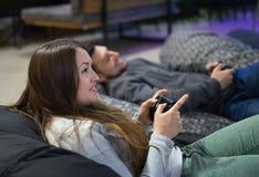 Amis heureux de couples jouant des jeux vidéo avec la manette se reposant sur la chaise de fauteuil poire Images stock