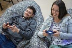 Amis heureux de couples jouant des jeux vidéo avec la manette se reposant sur la chaise de fauteuil poire Image libre de droits