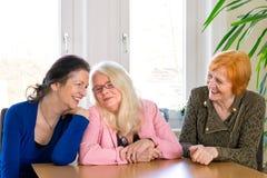 Amis heureux de femelle adulte s'asseyant à la table de salle à manger Photographie stock libre de droits