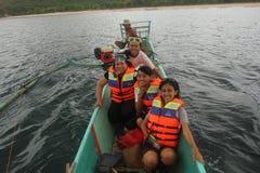Amis heureux de femme s'asseyant sur un bateau Image stock