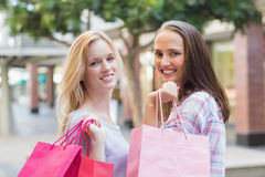 Amis heureux de femmes avec des paniers souriant à l'appareil-photo Photos stock