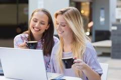 Amis heureux de femmes buvant du café et regardant l'ordinateur portable Images libres de droits
