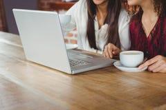 Amis heureux de femmes buvant du café et regardant l'ordinateur portable Image stock