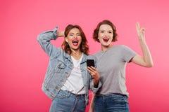 Amis heureux de femmes employant la musique de écoute de téléphone portable Images stock