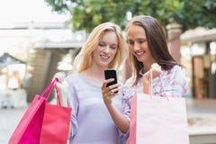 Amis heureux de femmes regardant le smartphone Image libre de droits