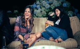 Amis heureux de femmes riant et buvant dans a Image stock