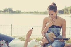 Amis heureux de femmes riant le media social de lecture rapide sur des périphériques mobiles Image stock