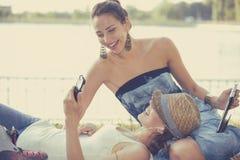 Amis heureux de femmes riant le media social de lecture rapide sur des périphériques mobiles Photos stock