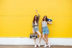 Amis heureux de femmes se tenant au-dessus du mur jaune Photographie stock libre de droits