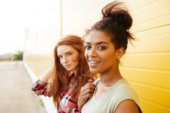 Amis heureux de femmes se tenant au-dessus du mur jaune Image stock