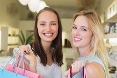 Amis heureux de femmes souriant à l'appareil-photo avec des paniers Photo libre de droits