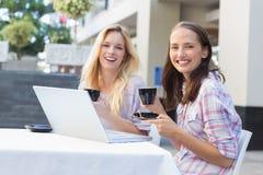 Amis heureux de femmes souriant à l'appareil-photo avec des tasses de café Image stock