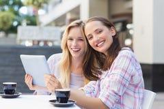 Amis heureux de femmes souriant à l'appareil-photo et tenant le comprimé Photographie stock