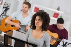 Amis heureux de groupe appréciant jouant la guitare et chantant ensemble Photos libres de droits