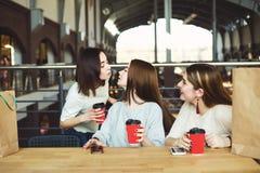 Amis heureux de salutation de femme au café Images stock