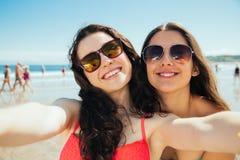 Amis heureux de selfie sur la plage Photographie stock