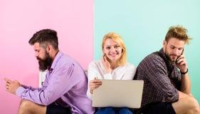 Amis heureux de société avec l'ordinateur portable mobile d'instruments Les hommes et la femme ont accès au réseau de partout mod Images stock