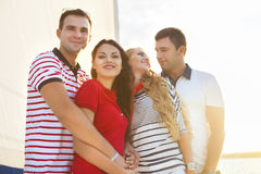 Amis heureux de sourire sur la plate-forme de yacht Image libre de droits