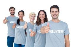 Amis heureux de volontaires faisant des gestes des pouces  Photo libre de droits