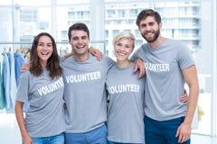 Amis heureux de volontaires souriant à l'appareil-photo Image libre de droits