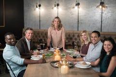 Amis heureux dinant dans le restaurant Images libres de droits