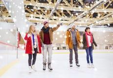 Amis heureux dirigeant le doigt sur la piste de patinage Photographie stock libre de droits