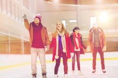 Amis heureux dirigeant le doigt sur la piste de patinage Images libres de droits