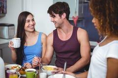 Amis heureux discutant à la table de petit déjeuner Photo libre de droits