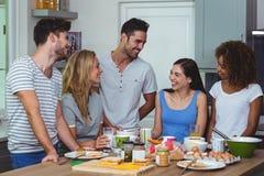 Amis heureux discutant tout en prenant le petit déjeuner Photos stock