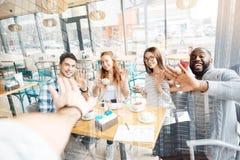 Amis heureux donnant cinq à la table Photos stock