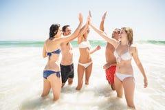 Amis heureux donnant de hauts cinq sur la plage Photos stock