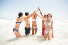 Amis heureux donnant de hauts cinq sur la plage Images stock