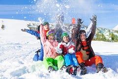 Amis heureux drôles avec des surfs des neiges jetant la neige Image stock
