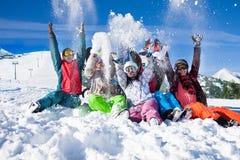 Amis heureux drôles avec des surfs des neiges jetant la neige Photo libre de droits