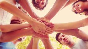 Amis heureux empilant des mains ensemble en parc banque de vidéos