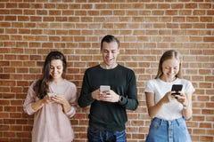 Amis heureux employant le concept social de media de smartphones Image stock