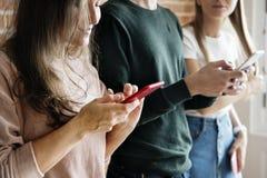 Amis heureux employant le concept social de media de smartphones Photographie stock libre de droits