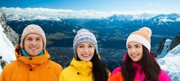 Amis heureux en hiver au-dessus des montagnes d'alpes Photographie stock libre de droits