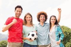 Amis heureux en parc avec le football Photo libre de droits