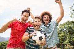 Amis heureux en parc avec le football Photographie stock libre de droits