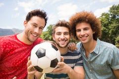 Amis heureux en parc avec le football Photo stock